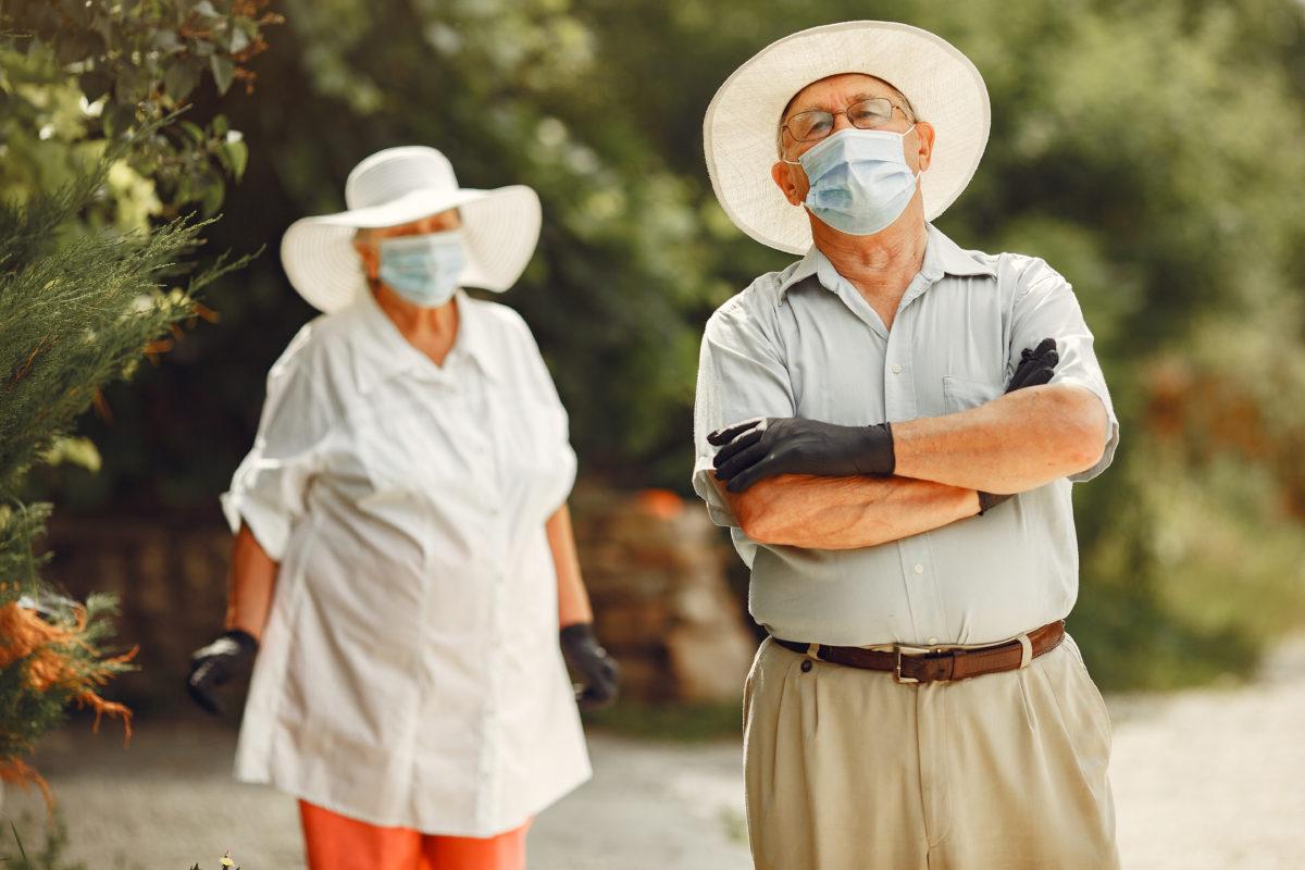 foto com arvores ao fundo e, na frente, há dois senhores, uma senhora no canto esquerdo usando roupas claras, chapéu e máscara, no outro lado há um senhor com camiseta azul clara, cinto, berumada, usando também um chapéu e máscara, ele está de braços cruzados, ilustrando idoso com covid