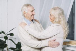 dois idosos na imagem com camisetas brancas, um na frente do outro, como se estivessem dançando