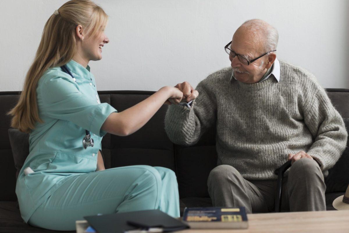 Uma mulher do lado esquerdo da foto com uma roupa azul de enfermeira sentada em um sofá e ao seu lado há um senhor de idade com roupas cinzas, careca e óculos cumprimentando a especialista em envelhecimento ativo com um gesto com as mãos
