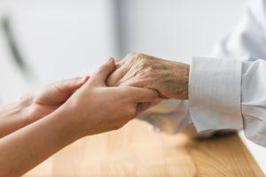duas mãos na imagem, uma do lado esquerdo mais jovem e do lado direito a mão está mais envelhecida