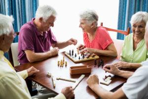dois senhores de idade sentados em uma mesa do lado esquerdo de uma mesa enquanto há duas senhoras sentadas do lado direito, eles estão jogando xadrez e dominó, sorrindo